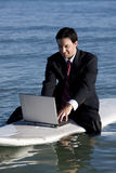 Businessman on Surfboard Stock Photos