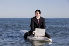 Businessman on Surfboard Stock Photography