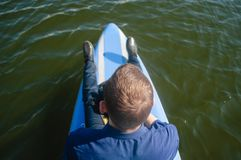 Businessman on a surfboard, a Young man in a shirt and shoes floating on the river on a paddleboard, the concept of finding. Opportunities, the idea of opening stock photography