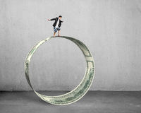 Businessman surfing and balancing on large money circle Stock Image
