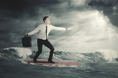 Businessman surfing on a cloudy day. Excited young businessman surfing on a cloudy day Royalty Free Stock Images