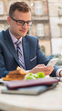 Businessman with surfing the internet of the tablet during breakfast. Royalty Free Stock Images