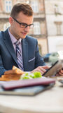 Businessman with surfing the internet of the tablet during breakfast. Stock Photos
