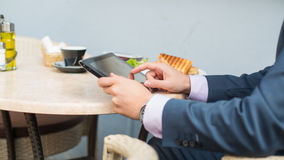 Businessman with surfing the internet of the tablet during breakfast. Stock Photography