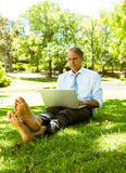 Businessman surfing on laptop. Mature businessman using laptop while relaxing on grass in park Stock Photography