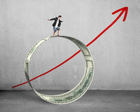 Businessman surfing on money circle with growing red arrow Stock Image