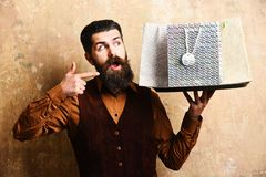 Businessman with surprised face points at presents for Xmas. Or birthday. Service and shopping concept. Waiter with silver packages on tray. Man with beard stock images