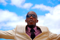 Businessman surprised portrait. Outdoor head portrait of an attractive African American businessman wearing suit, neck tie and black sunglasses with surprised Stock Photography