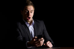 Businessman surprised about text messages. Handsome young businessman in dark suit sitting at office desk being surprised about text messages on mobile-phone Stock Photo