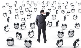 Businessman surrounded by alarm clocks Stock Image