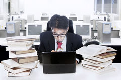 Businessman surrounded with books and computer. Young businessman is reading something at his laptop with shock surrounded with lots of books Royalty Free Stock Photography