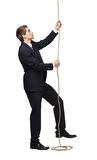 Businessman swarming up the rope Stock Photo