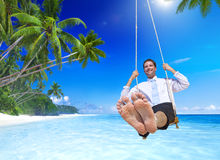 Businessman swinging at Tropical Beach Stock Image