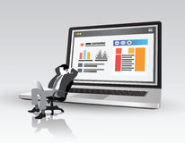 Businessman on swivel chair in front of laptop showing data Stock Image
