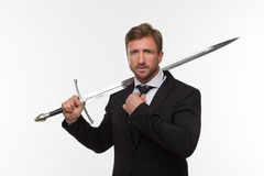 Businessman with sword. Isolated on white background. Handsome man in black business suit ready to have a battle Stock Photo