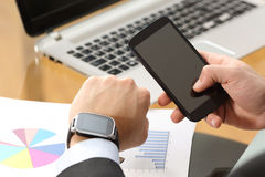 Businessman synchronizing a smart watch and phone Royalty Free Stock Images