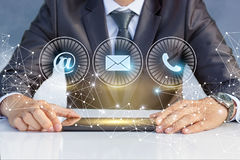 The businessman at the table and the contact us icons . Stock Photo
