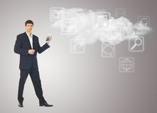 Businessman with tablet and the cloud with applications icons on Stock Images