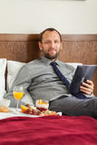 Businessman with tablet computer during breakfast. He is lying o Royalty Free Stock Photo