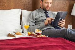Businessman with tablet computer during breakfast. He is lying o Stock Photography