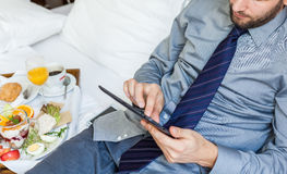 Businessman with tablet computer during breakfast. He is lying o Stock Images