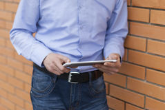 Businessman with tablet computer in the hands of the street. Royalty Free Stock Images