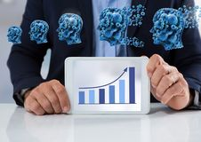 Businessman with tablet at desk with diagram of bar chart and cogs heads. Digital composite of Businessman with tablet at desk with diagram of bar chart and cogs Royalty Free Stock Photo