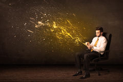 Businessman with tablet and energy explosion on background Royalty Free Stock Photography