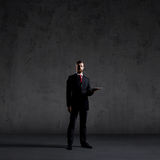 Businessman with a tablet on a grey background Royalty Free Stock Photography