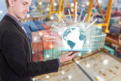 Businessman with tablet on hand show supply chain concept. Logistics import export over the world,container ship background. (Elements of this image furnished Royalty Free Stock Image