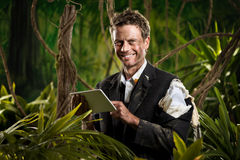 Businessman with tablet in the jungle Stock Images