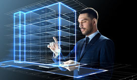 Businessman with tablet pc and building hologram Stock Photos