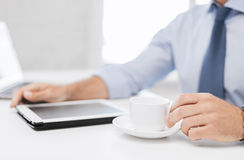 Businessman with tablet pc and coffee in office Stock Photography