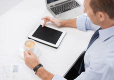 Businessman with tablet pc and coffee in office Stock Photo