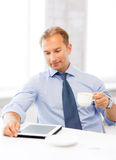 Businessman with tablet pc and coffee in office Royalty Free Stock Photos