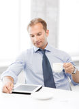 Businessman with tablet pc and coffee in office Royalty Free Stock Images