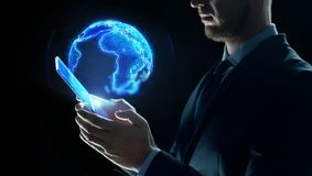 Businessman with tablet pc and earth hologram stock image