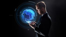 Businessman with tablet pc and earth hologram royalty free stock image