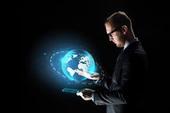 Businessman with tablet pc and earth hologram Royalty Free Stock Images