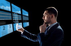 Businessman with tablet pc and exchange charts. Business, augmented reality and future technology concept - businessman in suit working with transparent tablet Royalty Free Stock Photo