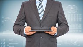 Businessman with tablet pc. Businessman holding tablet pc. On background of the high-tech graphs Royalty Free Stock Images