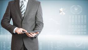 Businessman with tablet pc. Businessman holding tablet pc. On background of the high-tech graphs Stock Image