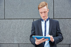 Businessman with tablet PC next to wall Stock Images