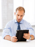 Businessman with tablet pc in office Stock Photo
