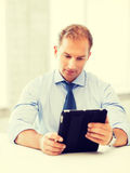 Businessman with tablet pc in office Stock Image
