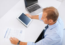 Businessman with tablet pc and papers in office Royalty Free Stock Photography
