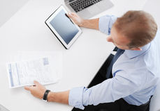 Businessman with tablet pc and papers in office Stock Photography