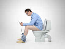 Businessman with tablet pc sitting on the toilet Royalty Free Stock Photo