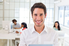 Businessman with tablet pc smiles to camera Royalty Free Stock Image