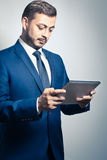 Businessman with tablet pc. Businessman using his tablet pc computer. Studio Shot Stock Photography